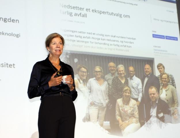 Utvalgsleder Ingrid Riddervold Lorange foran bilde av utvalget som nå bare har få uker på seg før rapporten skal overleveres til klima- og miljøminister Ola Elvestuen.